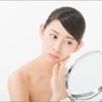 鏡を見て肌をチェックする女性