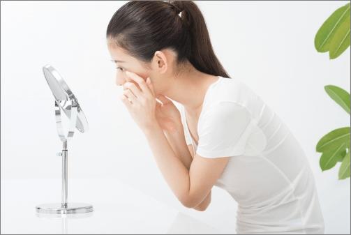 鏡で肌をチェックする女性(横顔
